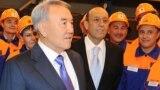 Нурсултан Назарбаев в бытность президентом Казахстана в сентябре 2012 года посещает электролизный завод в Павлодаре. По его левую руку — Александр Машкевич, один из основателей компании ENRC, которая подала в суд на британского журналиста Тома Берджеса, автора книги о коррупции