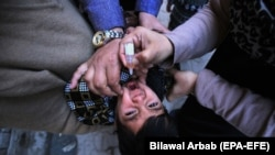 Медицинский работник вводит вакцину против полиомиелита детям во время кампании вакцинации от полиомиелита на дому в Пешаваре, 11 января 2021 г.