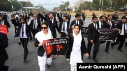 Lawyers display placards as they march along a street during an anti-France demonstration near the French Embassy in Islamabad on November 12.