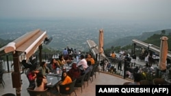People flock to a restaurant on Margalla Hills in Islamabad on August 10 after the government announced it would be lifting most of the country's remaining coronavirus restrictions.