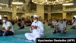 Kyrgyz Muslims wearing face masks and keeping a social distance of 1 1/2 meters pray in the Central Imam Serahsi Mosque in Bishkek on June 12.