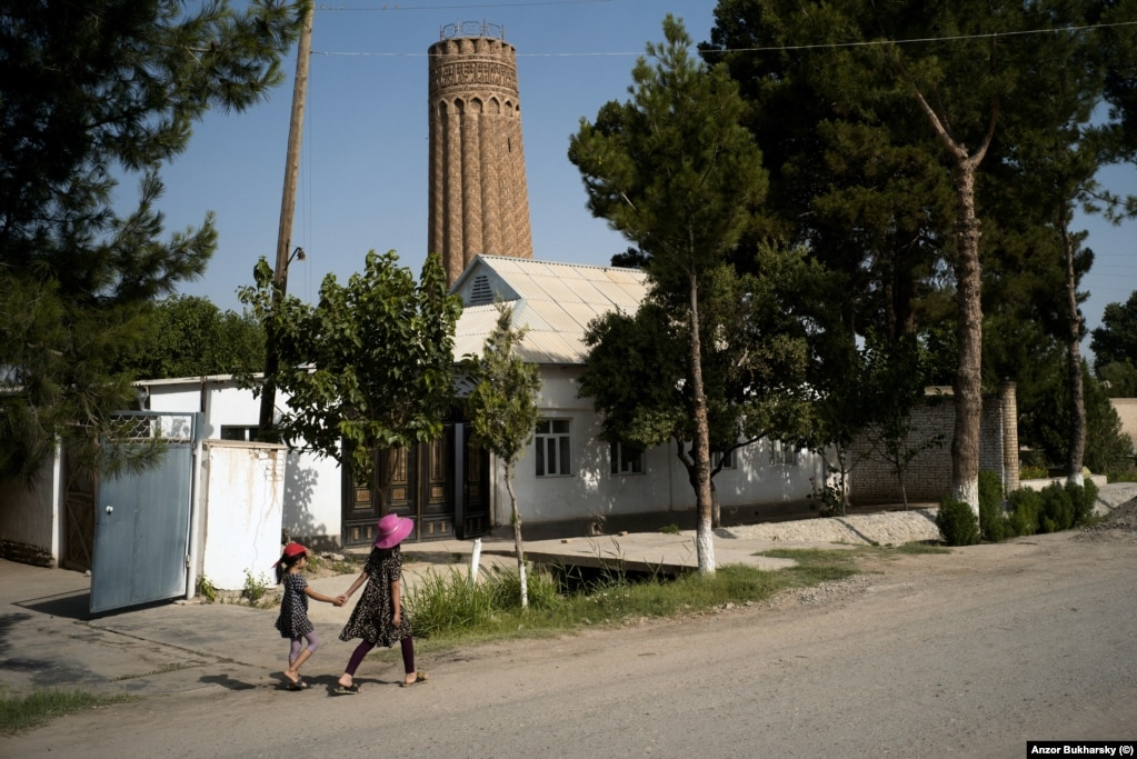 Two local girls walk near a 900-year-old minaret in the southern town of Minor, near the border with Afghanistan.