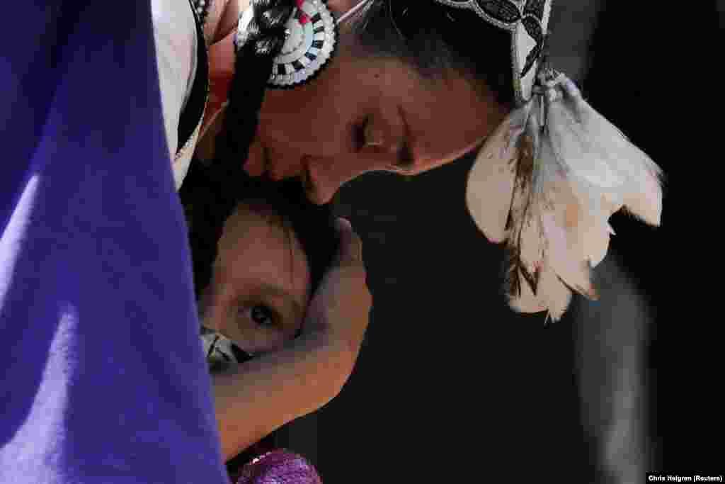 A kamloopsi iskola 1890 és 1978 között működött. Kanada legnagyobb bentlakásosindián iskolája volt, de az országban számos más helyen várták az őslakókat hasonló intézmények. A képen a megemlékezésen részt vevő egyik anya öleli meg gyermekét.