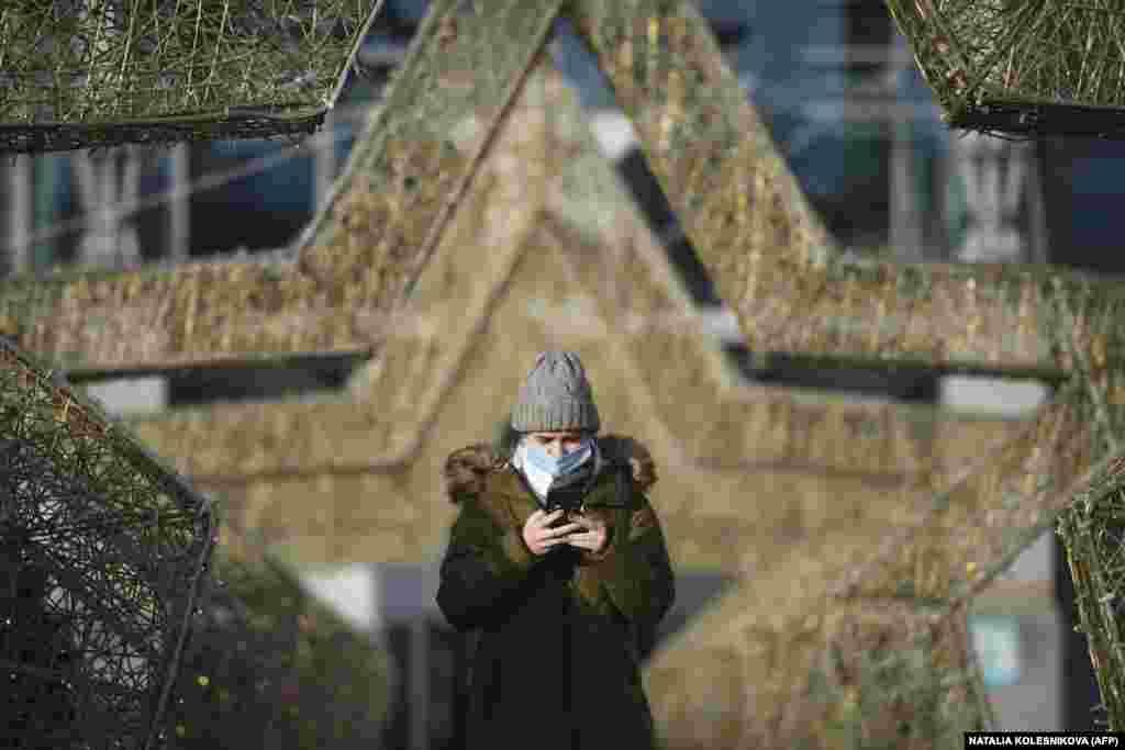 Жена со маска за лице шетајќи низ празничните украси во форма на ѕезда поставени за претстојните новогодишни и божиќни празници пред трговскиот центар во Москва на 11 декември 2020 година.