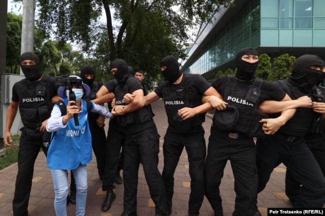 Правозащитница Инга Иманбай ведет прямую трансляцию рядом с сотрудниками полиции. Алматы, 6 июля 2021 года