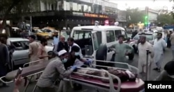 A screen grab shows people carrying an injured person to a hospital after the attacks at Kabul airport on August 26.