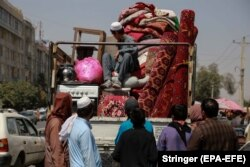 An Afghan man brings his household items to sell at a Kabul market on September 10, 2021. Afghans who plan to flee the country or are in need of cash to buy groceries and food resort to sell their belongings.