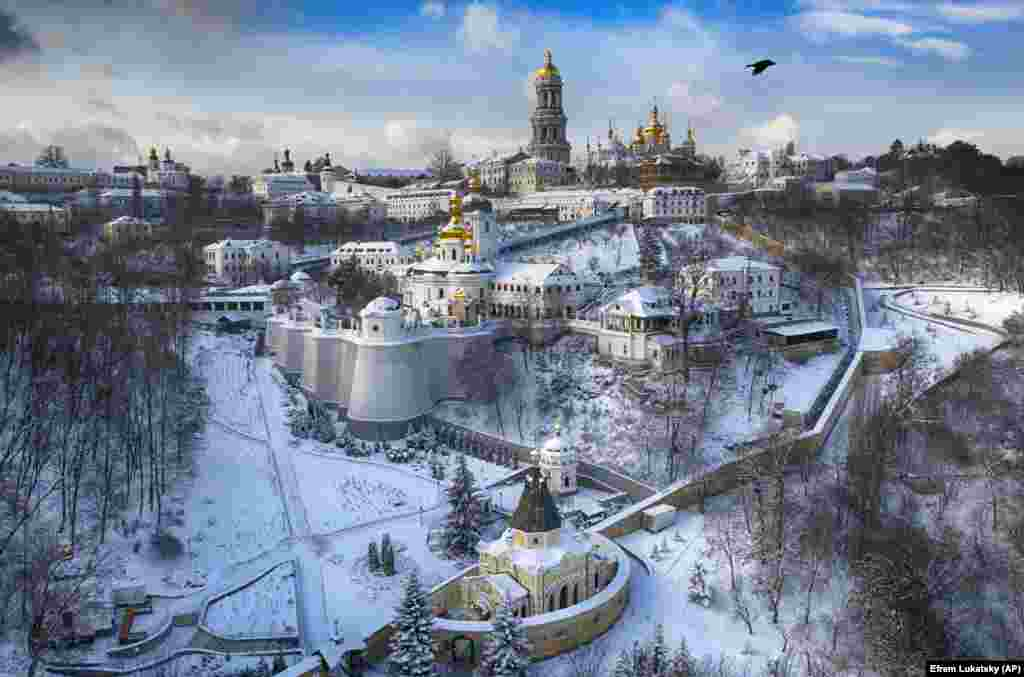 A bird flies near the 1000-year old Orthodox Monastery of Caves, covered with the first snow of winter in Kyiv on January 15. (AP/Efrem Lukatsky)
