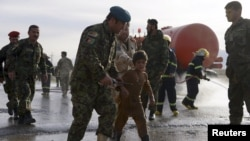 An Afghan National Army officer escorts a slightly injured boy from the site of a suicide attack on the outskirts of Mazar-i-Sharif on February 8.