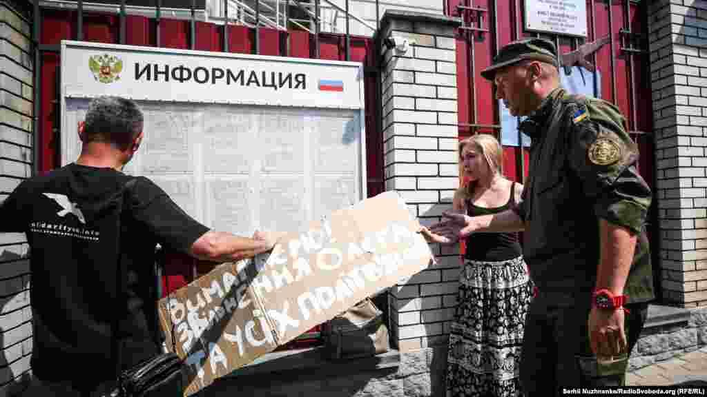 Плакат із основним своїм закликом активісти хотіли розмістити на дошці оголошень консульства Росії в Києві – охоронець не дозволив