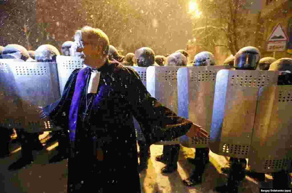 Динаятчы полиция менен чогулгандардын ортосунда сүйлөп жатат.