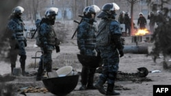Kazakh riot police patrol in the town of Zhanaozen on December 18. Locals say the number of dead from the December 16 violence is being deliberately under-reported.