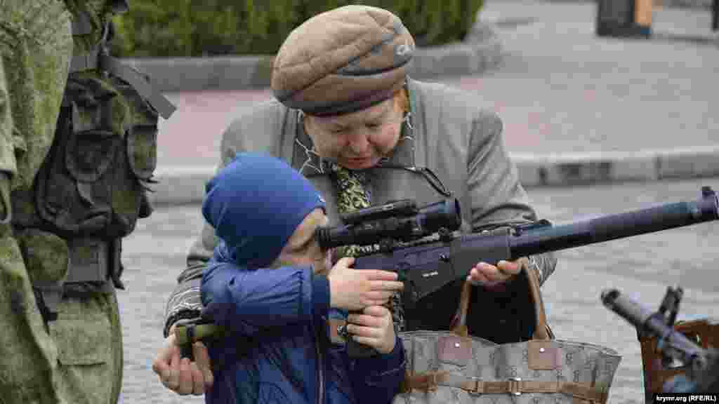 A woman helps a child aim a weapon during an exhibition of Russian military equipment in Sevastopol on April 12.