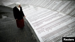 A Bosnian woman looks for the names of her dead relatives on a memorial plaque to the roughly 8,000 men and boys killed at Srebrenica.
