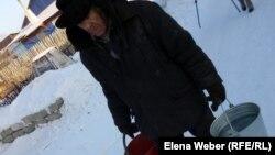 Пожилой мужчина несет домой воду, набранную из колодца. Темиртау, 20 декабря 2012 года.