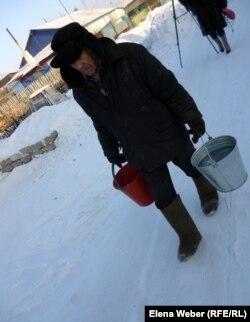 Пожилой мужчина несет ведра с водой. Темиртау, 20 декабря 2012 года.