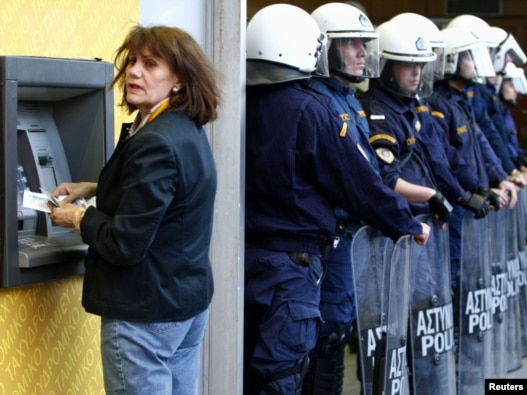 A woman makes a transaction at an ATM during a rally against austerity measures outside the Finance Ministry in Athens on April 29.