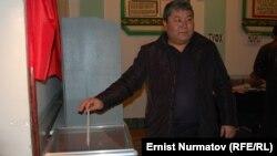 Мэр Оша Мелис Мырзакматов бросает свой бюллетень в урну на местных выборах. Ош, 4 марта 2012 года.