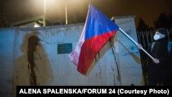 Демонстрант држи знаме на Република Чешка пред sид на руската амбасада во Прага, испрскан со кечап за време на протестот организиран од група активисти, Прага, на 17 април 2021 година.
