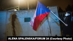A protester holds a Czech national flag in front of the walls of the Russian Embassy in Prague on April 18. Protesters splashed ketchup on the walls of the embassy to call attention to the deaths of the two people in a 2014 arms depot explosion the Czechs now blame on Russian agents.
