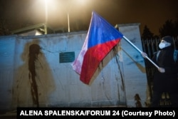 A protester holds a Czech national flag in front of the walls of the Russian Embassy in Prague. Protesters splashed ketchup on the walls of the embassy to call attention to the deaths of the two people in the 2014 explosion.