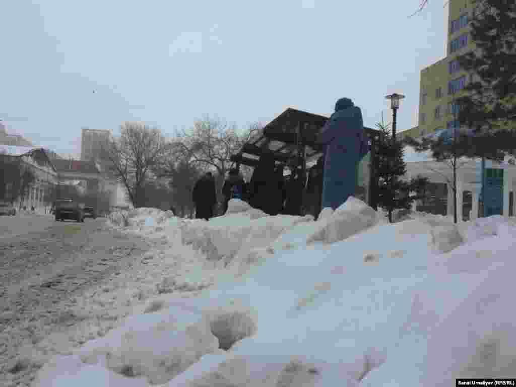 «Артем» базары маңындағы аялдама. Жолаушылар автобусқа отыру үшін жол жиегінде үйілген қардан аттап өтеді. Нұр-Сұлтан, 28 қаңтар 2020 жыл.