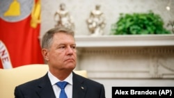 U.S. -- Romanian President Klaus Iohannis listens as President Donald Trump speaks in the Oval Office of the White House, Washington, August 20, 2019