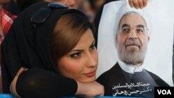 İranlı qadın Hassan Rohaninin plakatını tutub