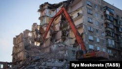 Workers dismantle a section of a building in Magnitogorsk hit by a blast on December 31, 2018.