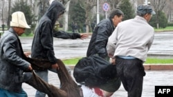 Protesters carry a victim of the security forces' crackdown on the crowd outside the main government building in Bishkek on April 7, 2010, when officials say 87 people died.