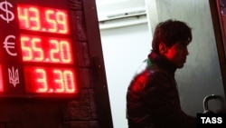 A man walks past a board showing currency exchange rates in Moscow on October 29.