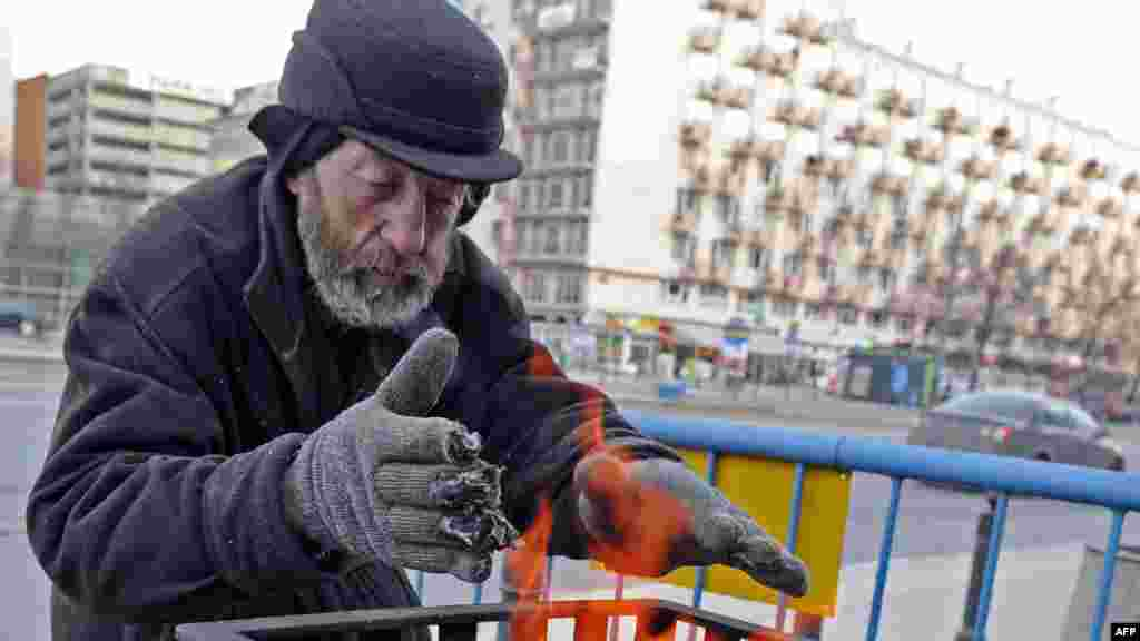 A homeless man warms up near an outside coal fire on a street in Warsaw.