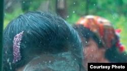 """Фото девочки, лицо которой покрыто кислым молоком для защиты от солнечного ожога. Фото из альбома Умиды Ахмедовой """"Женщины и мужчины: от рассвета до заката""""."""