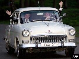 Бывший президент США Джордж Буш-младший едет за рулем автомашины 'Волга' 1956 года, принадлежащей бывшему президенту России Владимиру Путину. Подмосковье, 8 мая 2005 года.