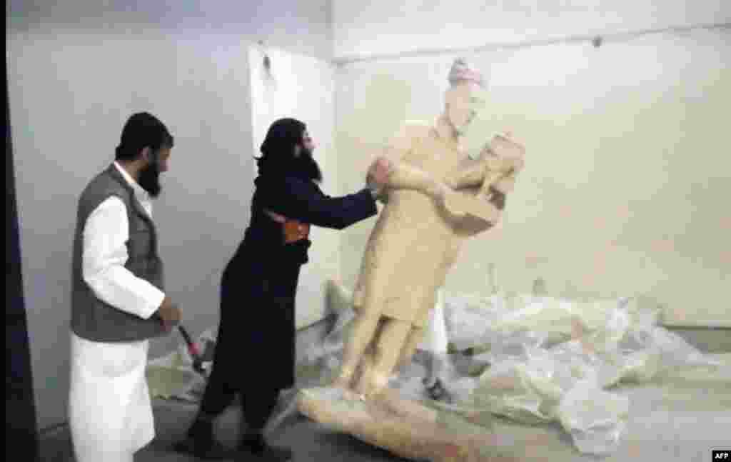 """Бунтовниците на Ислямска държава бутат статуя в музея в Мосул, северен Ирак, през 2014 или 2015 г. Мюсюлманските екстремисти унищожават множество антични съкровища с чукове и инструменти в музея, наричайки ги """"идолопоклоннически""""."""