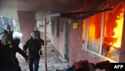 Pro-Russia protesters wearing gas masks storm a regional police building as one prepares a Molotov cocktail in Horlivka.
