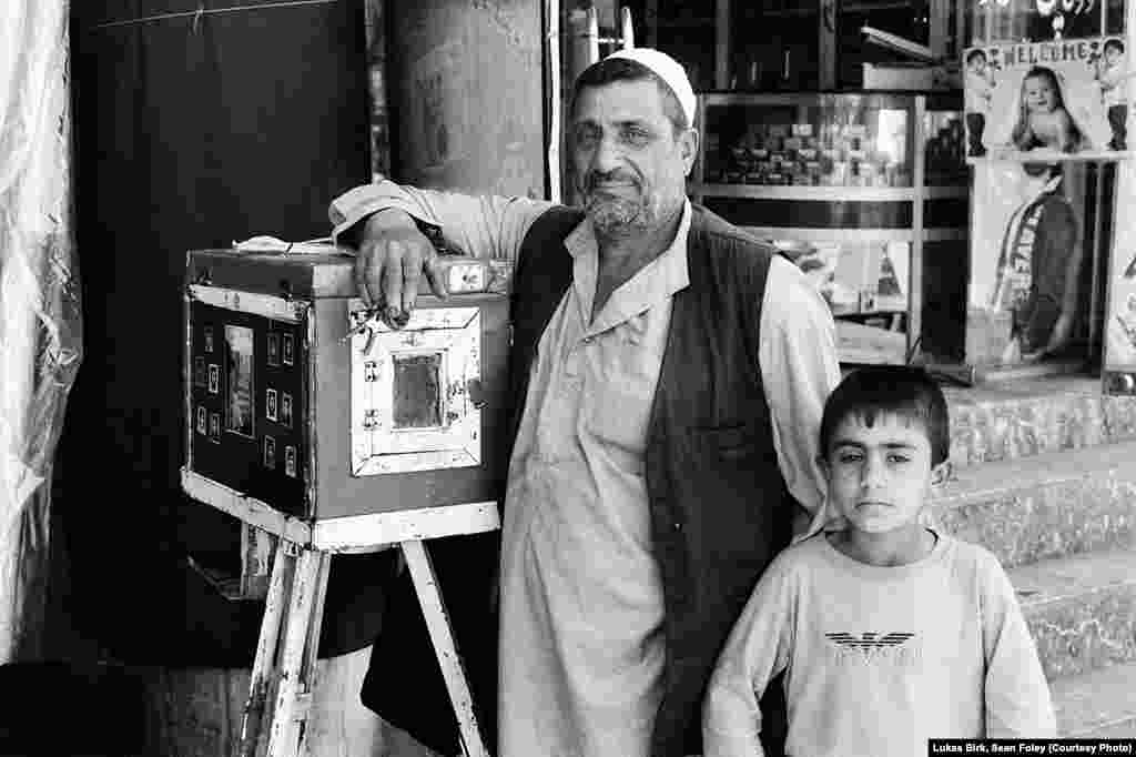 OPENING ARTICLE PHOTO -- 14_Roh Ullah, a box camera photographer with son. Kabul, 2011.