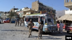Pakistani security officials inspect the site of an incident were unknown assailants opened fire on a bus in Hazara Ganji area of Quetta on 23 October 2014.