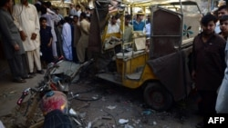 Locals gather at the site of an overnight bomb blast in Karachi on March 15.