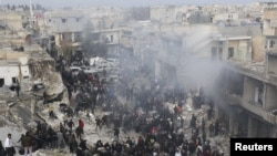 People gather at a site hit by what activists said was missiles fired by a government fighter jet from forces at the souk of Azaz, north of Aleppo, on January 13.