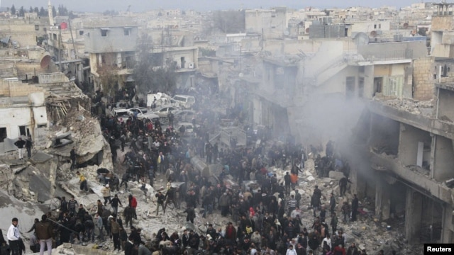 People gather at a site hit by missiles fired by a government air force fighter jet in Azaz, north of Aleppo, on January 13.
