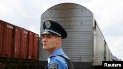 Украинский милиционер охраняет поезд с вагонами-рефрижераторами, в которых находятся тела пассажиров упавшего лайнера. Харьков, 22 июля 2014 года.