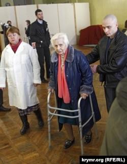 Пожилая женщина в сопровождении медработника на избирательном участке №1 в Симферополе, 16 марта 2014 года