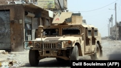 A U.S.-made military vehicle used by the Syrian Democratic Forces drives through an eastern area of the embattled Syrian city of Raqqa last month.