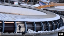 Workers paint the exterior of the track at the Sanki Sliding Center in preparation for the start of the Sochi Games last week.