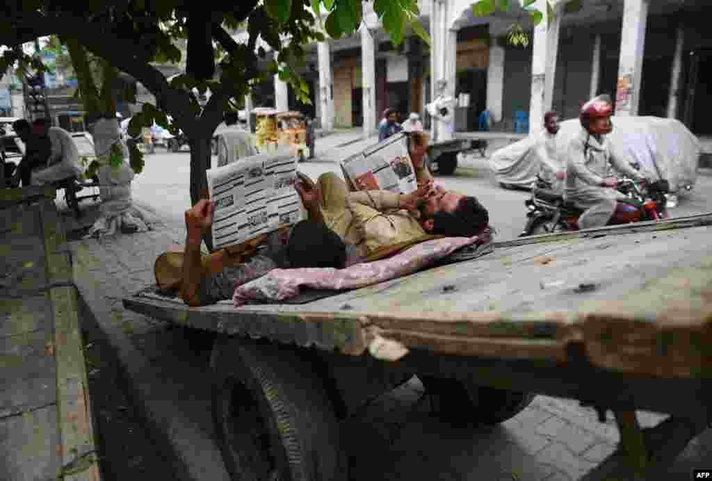 Pakistani laborers read newspapers as they rest on a cart at a market in Rawalpindi. (AFP/Farooq Naeem)
