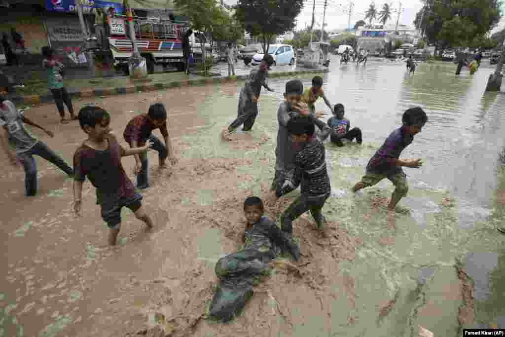 Pakistani boys play in a flooded street after heavy rainfall in Karachi. (AP/Fareed Khan)