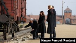 U.S. Vice President Mike Pence (kneeling), with wife Karen, and Polish President Andrzej Duda at the Nazi's Auschwitz extermination camp.