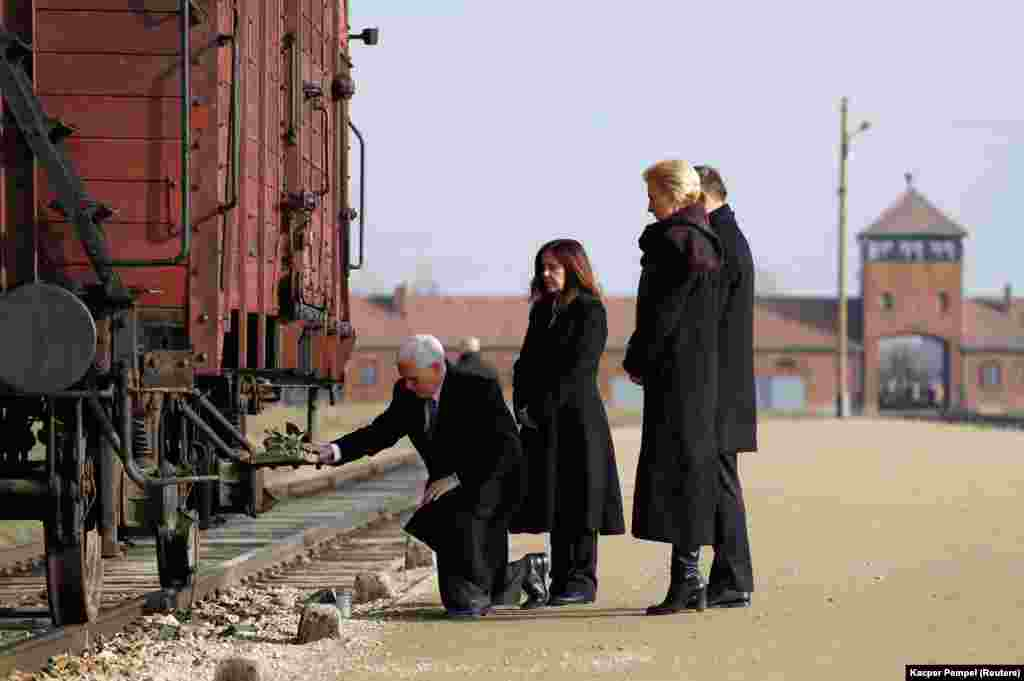U.S. Vice President Mike Pence with his wife, Karen, and Poland's President Andrzej Duda with first lady Agata Kornhauser-Duda lay flowers on a train wagon as they visit the former Nazi German concentration and extermination camp Auschwitz II-Birkenau, near Oswiecim, Poland. (Reuters/Kacper Pempel)