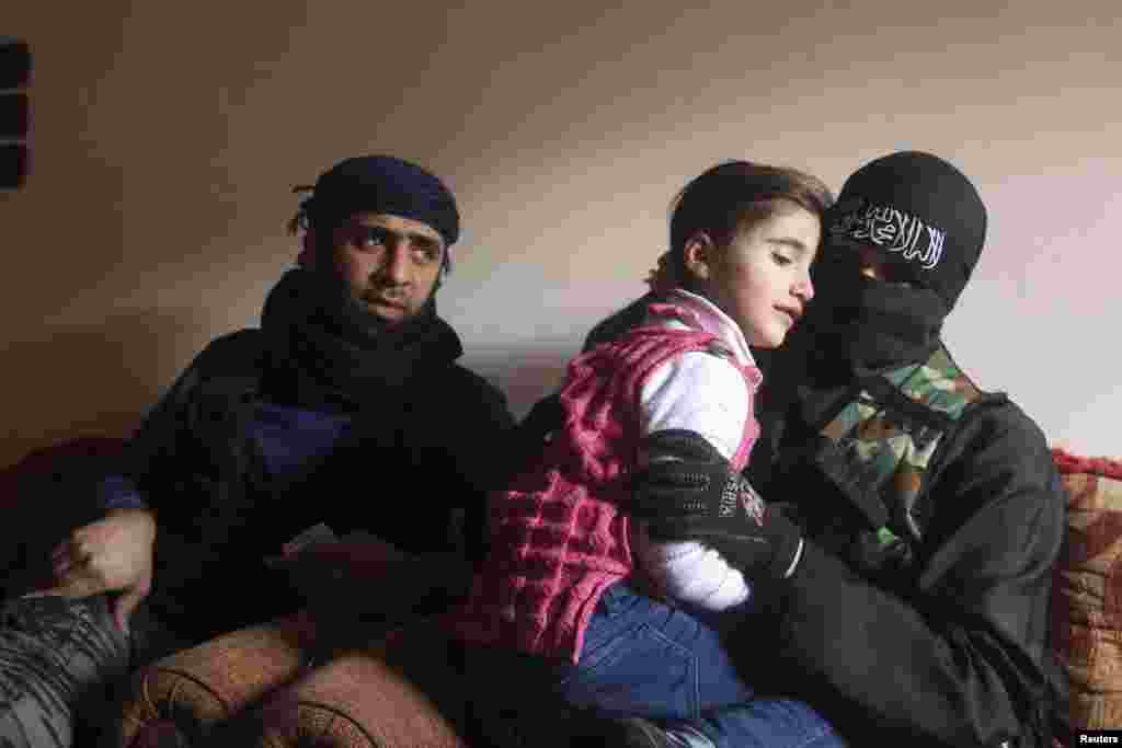 Um Jaafar, a woman fighter in the Free Syrian Army, sits with her husband, Abu Jaafar, a Sawt al-Haq (Voice of Rights) battalion commander, and their daughter Faten at their home in Aleppo. Um Jaafar was a hairdresser before the revolution. (Reuters/Muzaffar Salman)